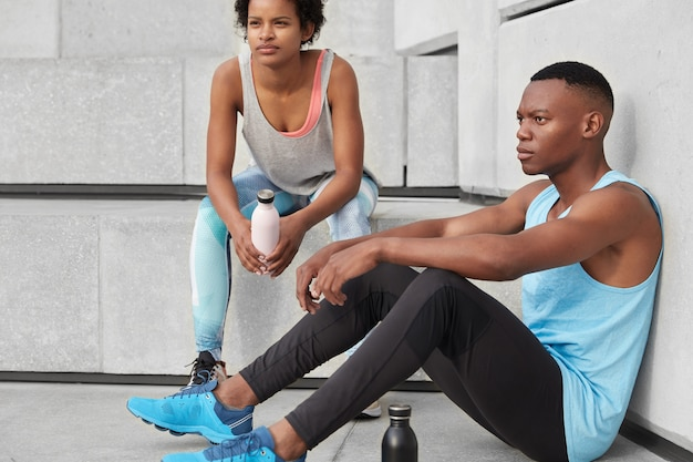 동기 부여가 된 어두운 피부를 가진 남자와 그의 여성 동반자의 사진, 계단에서 함께 포즈를 취하고, 야외 심장 훈련 후 휴식을 취하고, 물을 마시고, 운동 체형을 가졌으며, 뛰어 올라갑니다. 라이프 스타일 컨셉