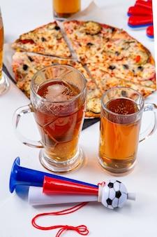 空の白い背景の上の泡ビール、ピザ、パイプとマグカップの写真