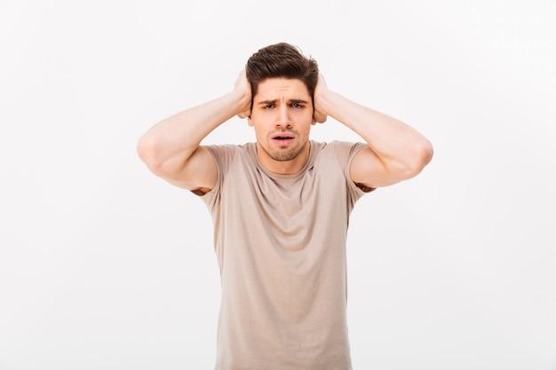 白い壁に分離された30代の筋肉の成人男性の写真彼の頭をつかんでまたは混乱で耳を覆う