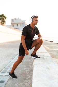 Фотография мускулистого мужчины 30-х лет в шортах и футболке, который тренируется на берегу моря и слушает музыку через беспроводные наушники на рассвете