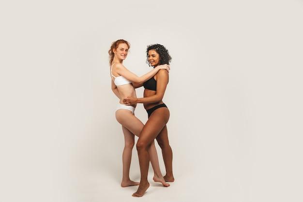 자연적인 다민족 여성의 사진, 신체 긍정적. 속옷에 페미니스트 여성은 흰색 배경에 고립 서로 포옹