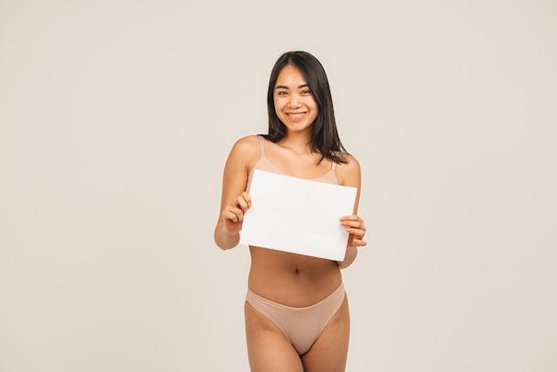 자연 여자 얼굴의 사진, 속옷을 입고 하얀 접시를 보유하고 있습니다. 흰색 배경 위에 격리.