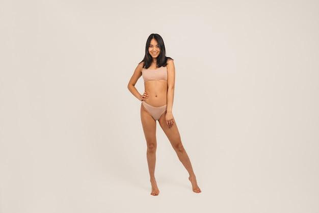 자연 여자 얼굴의 사진, 속옷을 입는다. 여성 스탠드 흰색 배경 위에 절연입니다.
