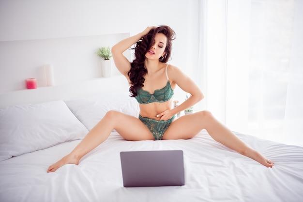 장난 꾸러기 뜨거운 미녀 재택 검역 온라인 노트북 채팅 확산 다리 쇼 레이스 팬티가 카메라에 자위하는 사진은 실내에서 흰색 린넨 시트에 앉아 비키니를 입고