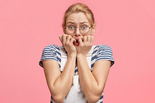 На фото нервная женщина кусает ногти и напряженно смотрит в камеру