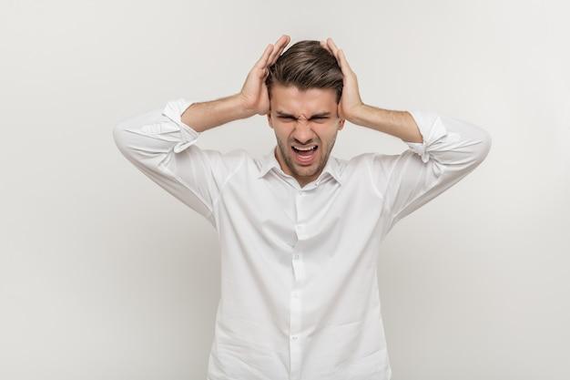 흰색 배경에 고립 된 두통으로 긴장된 비명을 지르는 젊은 남자의 사진