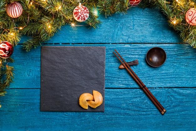 Фото новогодних веток пихты, черная доска, палочки для суши, печенье с предсказанием на синем деревянном фоне