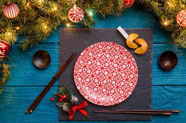 Фото новогодних веток пихты, черная доска, палочки для суши, печенье с предсказаниями, тарелки с красным узором на синем деревянном фоне