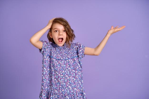 Фото красивой изумленной маленькой девочки, изолированной на фоне фиолетового цвета лаванды Premium Фотографии