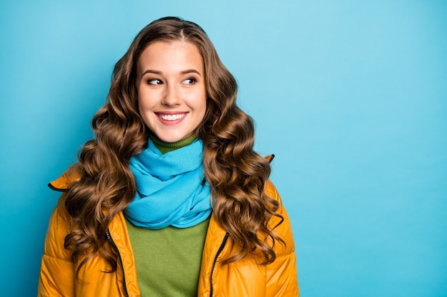 素敵な巻き毛の女性が横に空いているスペースを探している写真晴れた冬の日のストリートルックはカジュアルな黄色の暖かいオーバーコート青いスカーフ緑のプルオーバー孤立した青い色の壁を着用してください