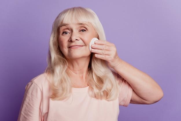 좋은 노부인의 사진은 면 스펀지를 사용하여 보라색 배경에서 화장을 제거합니다