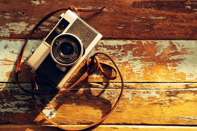ノスタルジア - 古い木製の背景にヴィンテージフィルムカメラの写真。