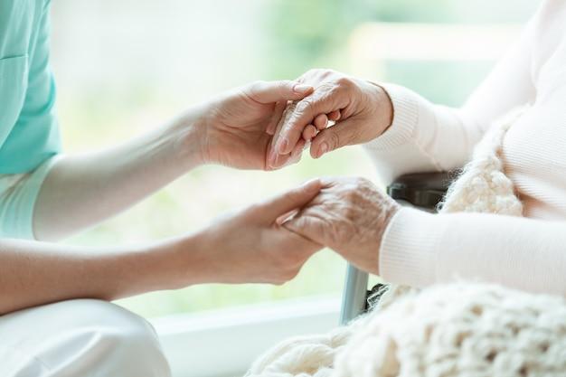 塗られた爪で彼女の女性患者の手を握っている看護師の写真