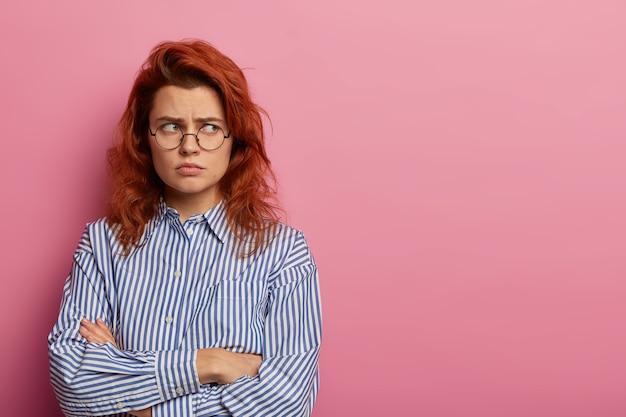 불쾌한 불쾌한 화난 여성의 사진은 모욕적 인 표정으로 서서 손을 교차하고 멀리 보면서 울고 둥근 안경과 파란색 줄무늬 셔츠를 입습니다.