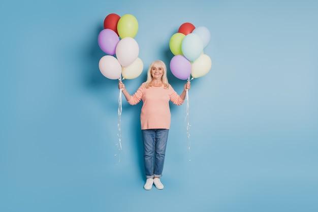 Фотография старухи держит красочные воздушные шары в розовом джемпере на синем фоне