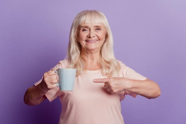 보라색 배경에 고립 된 노파 홀드 포인트 핑거 차 커피 컵의 사진