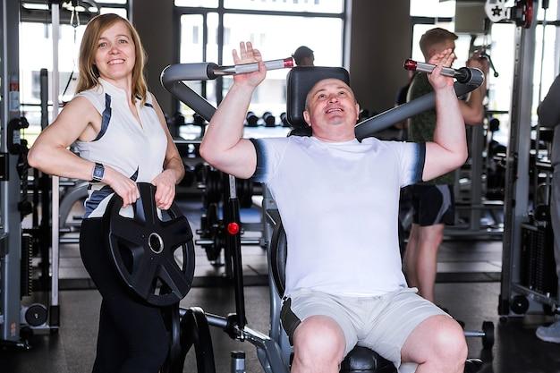 Фотография пожилой пары в тренажерном зале. мужчина делает упражнение на руки и плечи.
