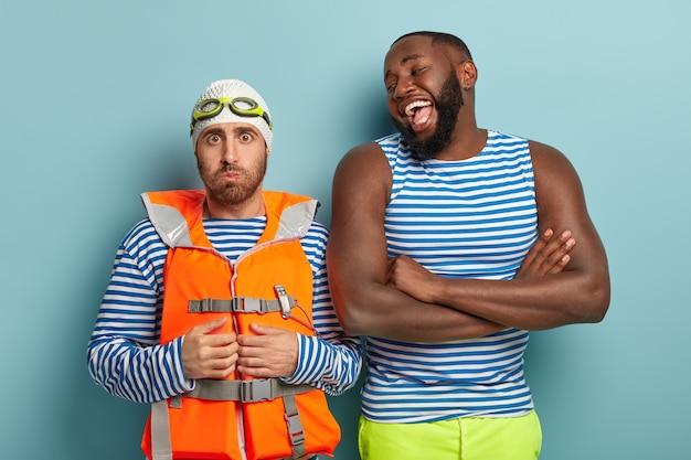 На фото оптимистичный темнокожий мужчина смеется над лучшим другом, который готовится к первому плаванию