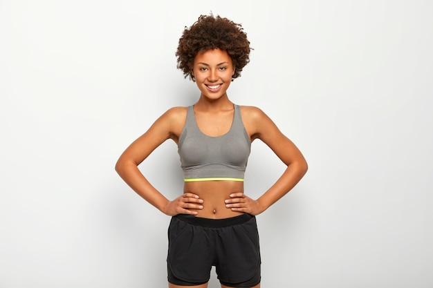 낙관적 인 어두운 피부 스포티 한 여자의 사진은 허리에 손을 유지하고 행복하게 미소 짓고 스포츠 브래지어와 검은 색 반바지를 입고 흰색 배경 위에 절연