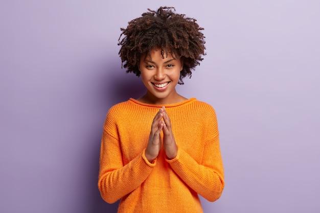 낙관적 인 어두운 피부를 가진 여성의 사진에는 아프로 헤어 스타일이 있고 손바닥을 모으고 넓게 웃으며 만족합니다.