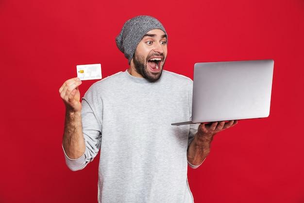 Фотография оптимистичного парня 30-х годов в повседневной одежде, держащего кредитную карту и серебряный ноутбук изолированы