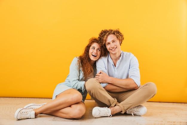 楽観的な幸せなカップルの男性と女性が一緒に床に座って、黄色の背景で隔離の笑顔と抱擁の写真