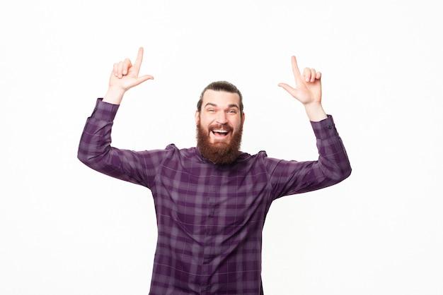 Фотография оптимистичного счастливого молодого бородатого мужчины, указывающего вверх