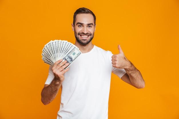 Фотография оптимистичного мужчины 30-х годов в повседневной одежде, держащего кучу денег, изолированные