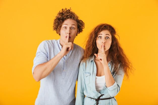 黄色の背景の上に分離された、笑顔で口に指を保持している基本的な服の楽観的な人々の男性と女性の写真