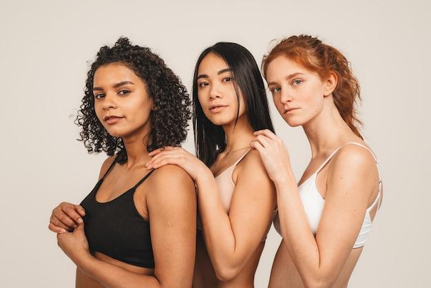 낙관적 인 젊은 여성의 사진, 다인종 친구들은 속옷을 입고 서로 포옹하고 사랑을 보여줍니다.