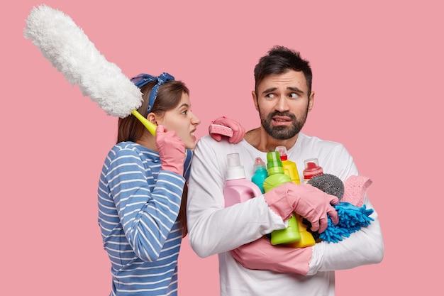 분노한 예쁜 아내의 사진은 성가심으로 남편에게 소리 질러 그의 게으름에 대해 불평하고 브러시를 운반합니다.