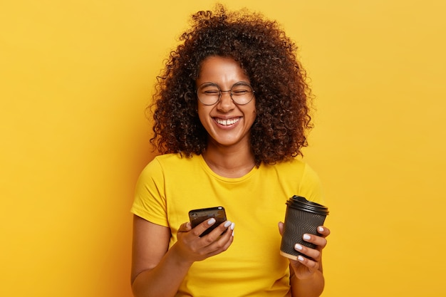 과도하게 표현 된 편안한 검은 머리 여성의 사진은 카푸치노 테이크 아웃 컵을 들고, 온라인 파티에서 재미있는 사진을보고, 현대 전자 장치를 사용하고, 화상 회의를 만들고, 캐주얼하게 옷을 입습니다.
