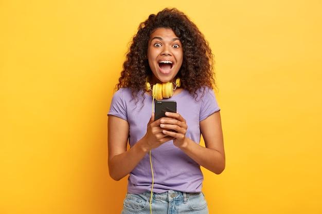 Фотография чрезмерно эмоциональной молодой девушки с афро-прической, позирующей на фоне желтой стены