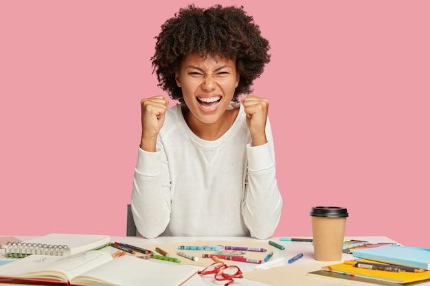 기뻐하는 아프리카 계 미국인 건축가의 사진은 주먹을 쥐고, 넓게 미소를 짓고, 얼굴을 가늘게 뜨고 있습니다.