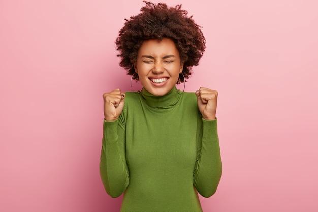Фотография обрадованной афро-женщины с торжеством сжимает кулаки, широко улыбается, радуется новому достижению