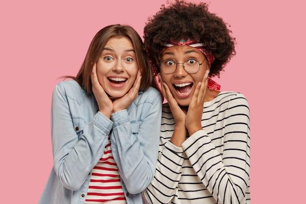 大喜びの興奮した二人の女性の写真は幸せで叫び、頬に手を保ちます
