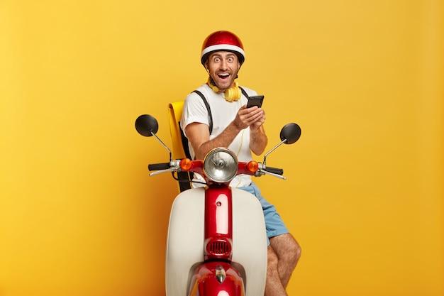 赤いヘルメットとスクーターで大喜びのハンサムな男性ドライバーの写真