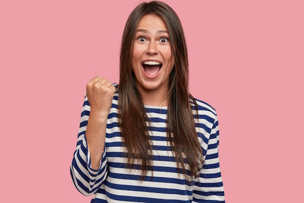 На фото обрадованная женщина чувствует себя чемпионкой, показывает победный жест, поднимает сжатые кулаки.