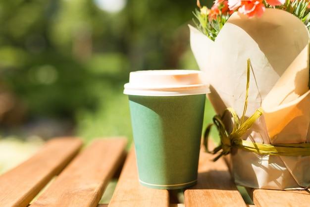 야외 테이블에 종이 커피 머그의 사진
