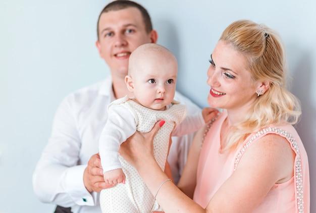 小さな子供を持つ親の写真が青い壁に向かってポーズをとっています