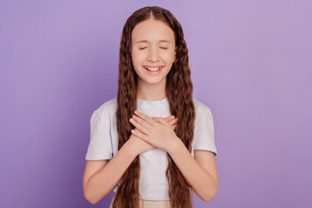 평화로운 귀여운 작은 소녀의 사진은 보라색 배경에 고립 된 손을 잡고 심장