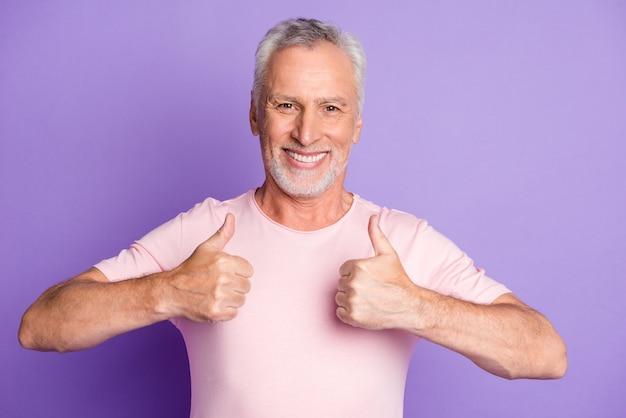 年金受給者のおじいちゃんが2本の腕を上げる写真は親指を立ててピンクのtシャツを着用します孤立した紫色の背景