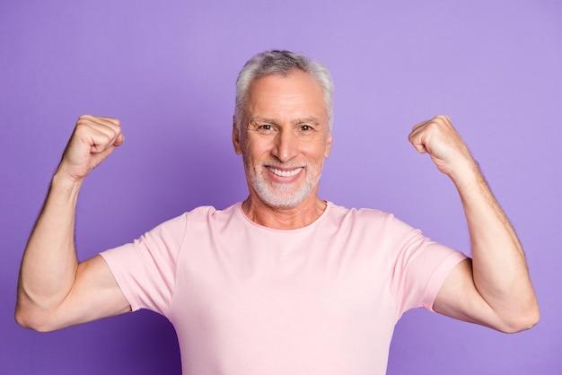 Фото дедушки пенсионера поднять две руки показать мышцы носить розовую футболку изолированный фиолетовый цвет фона