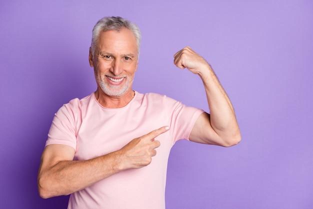 Фото пенсионера старик поднять руку прямым пальцем продемонстрировать бицепс носить розовую футболку изолированный фиолетовый цвет фона