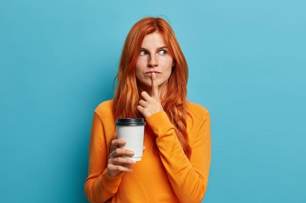 物思いにふける格好良い生姜の女性の写真は、唇に指を置き、何かについて深く考え、明日の計画を立ててコーヒーをテイクアウトします。美しい赤い髪の女性は屋内でお茶を飲みます