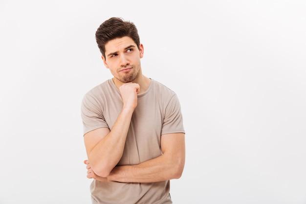 Фото задумчивого человека подпирая подбородок и позирует в сторону с серьезным взглядом, изолированных на белой стене