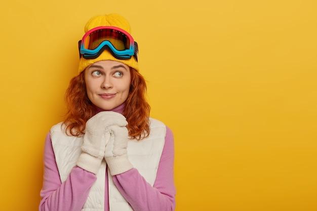 物思いにふける赤毛の女性観光客の写真は、スノーボードを楽しんで、黄色の背景に立ち、白い手袋と保護スキーゴーグルを着用しています