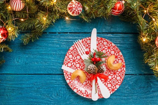 松の枝、赤い模様のプレート、予測クッキー、フォーク、ナイフ、青い木製の背景にクリスマスの装飾の写真