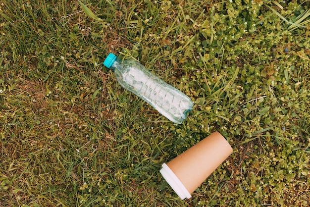 푸른 잔디에 플라스틱 병과 종이 커피 컵의 사진