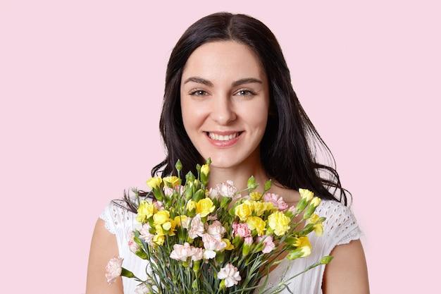 心地よく見える暗い髪のヨーロッパの女性の写真は官能的に微笑し、柔らかな肌、良い一日を楽しんで、春の花束を受け取り、バラ色の壁の上に孤立した自然の美しさを持っています。